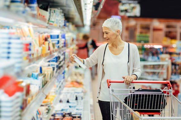 Frau beim Einkauf im Supermarkt mit Plastikverpackungen